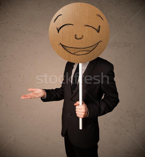 Businessman holding a smiley face board Stock photo © ra2studio