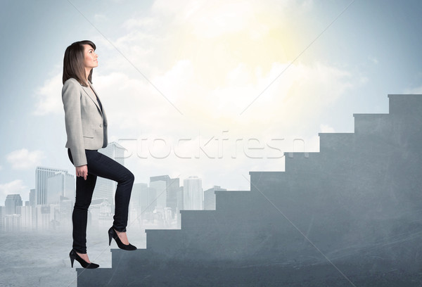 Businesswoman climbing up a concrete staircase concept Stock photo © ra2studio