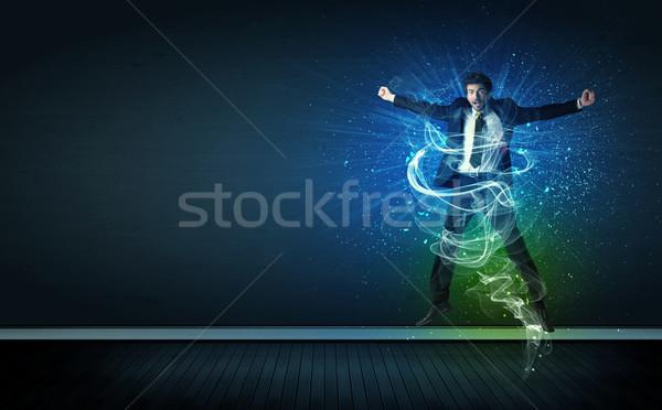 Tehetséges derűs üzletember ugrik izzó energia Stock fotó © ra2studio