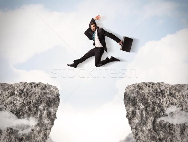 Grappig zakenman springen rotsen kloof man Stockfoto © ra2studio