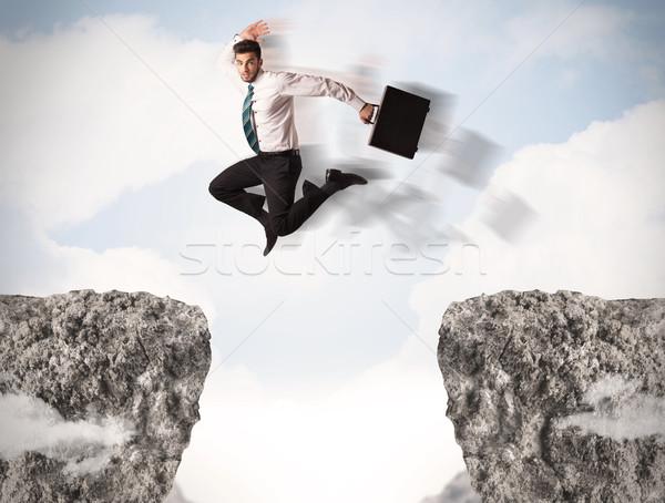 Komik iş adamı atlama kayalar boşluk iş Stok fotoğraf © ra2studio