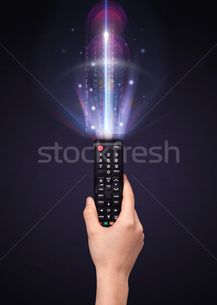 Stock photo: Hand with remote control and shining numbers
