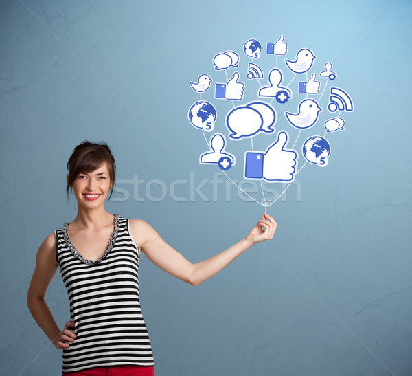 Pretty woman holding social icon balloon Stock photo © ra2studio