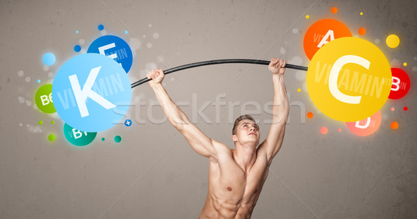 muscular man lifting colorful vitamin weights Stock photo © ra2studio