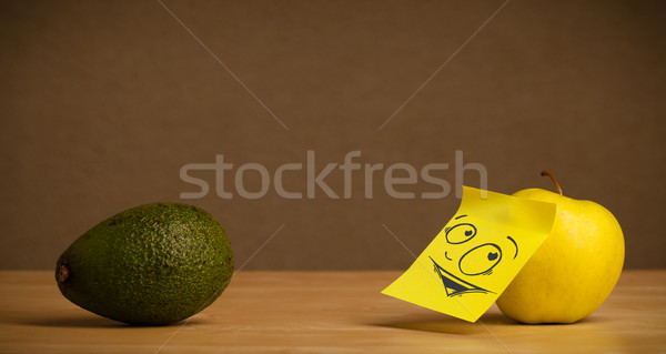 Stock photo: Apple with post-it note looking curiously at avocado