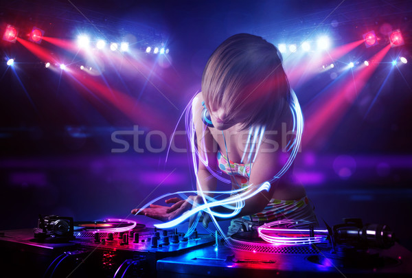 Disc jockey girl playing music with light beam effects on stage Stock photo © ra2studio