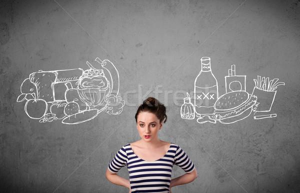 Woman standing between healthy and unhealthy foods Stock photo © ra2studio