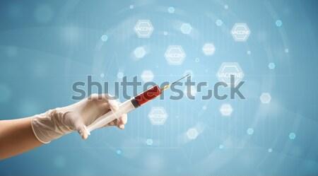 Female doctor holding syringe Stock photo © ra2studio