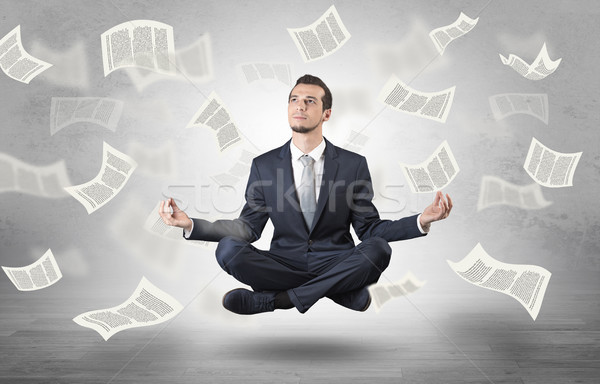 Businessman meditating with flying paper concept Stock photo © ra2studio