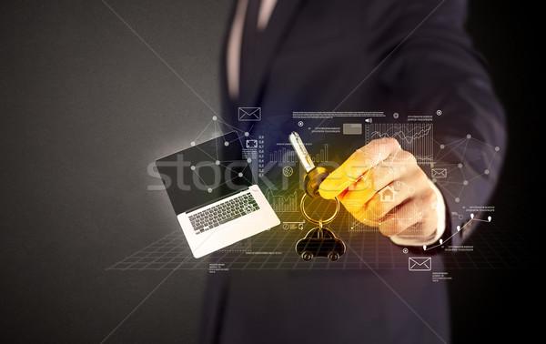 Businessman holding keys with graphs around Stock photo © ra2studio
