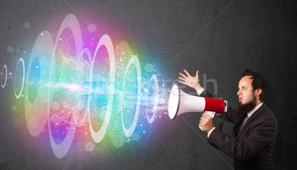 Man yells into a loudspeaker and colorful energy beam comes out Stock photo © ra2studio