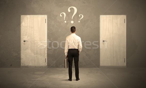 Businessman standing in front of doors Stock photo © ra2studio
