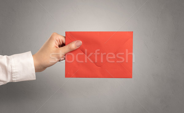 Hand holding envelope with empty wall background Stock photo © ra2studio