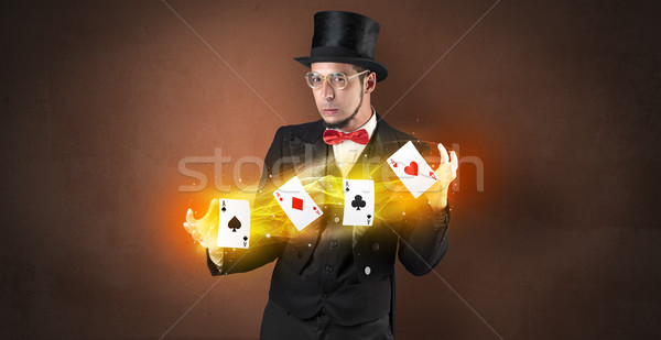 Illusionist making trick with magical play cards Stock photo © ra2studio