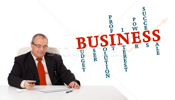 businesman sitting at desk and holding a mobilephone with business word cloud, isolated on white Stock photo © ra2studio