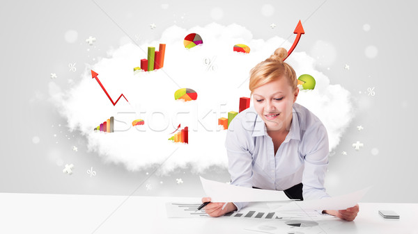 Beautiful young businesswoman with cloud in the background containing colorful diagrams Stock photo © ra2studio