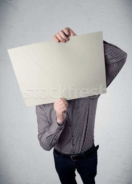Businessman holding in front of his head a paper with copy space Stock photo © ra2studio