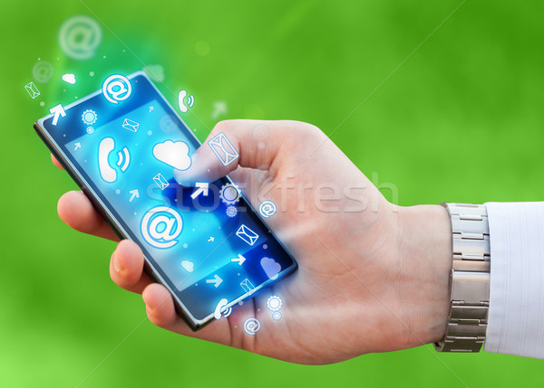 Business man holding smart phone with media icons Stock photo © ra2studio