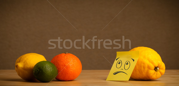 Lemon with sticky post-it note looking sadly at citrus fruits Stock photo © ra2studio