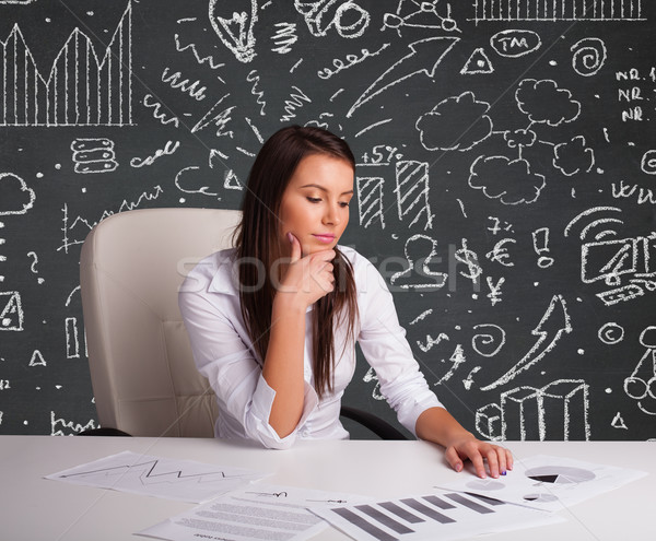 Businesswoman sitting at desk with business scheme and icons Stock photo © ra2studio
