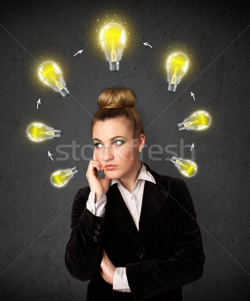 Young woman thinking with lightbulb circulation around her head Stock photo © ra2studio