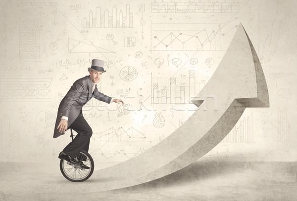 Happy business man riding a monocycle up on an arrow  Stock photo © ra2studio
