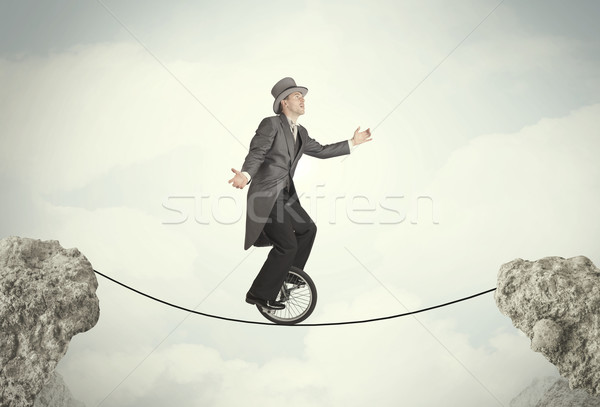 Stock photo: Brave business man riding an mono cycle between cliffs