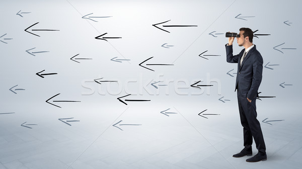 Man looking with binoculars and arrows around Stock photo © ra2studio