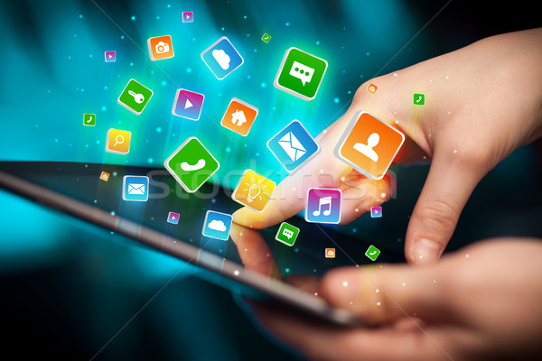 Hand using tablet with application icons flying around Stock photo © ra2studio