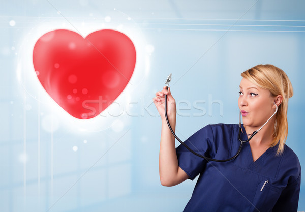 Young nurse healing a red heart Stock photo © ra2studio