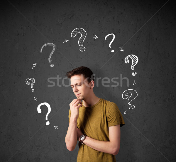 Thoughtful young man with drawn question marks circulating around his head Stock photo © ra2studio