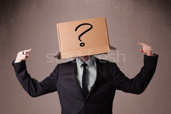 Businessman gesturing with a cardboard box on his head with ques Stock photo © ra2studio