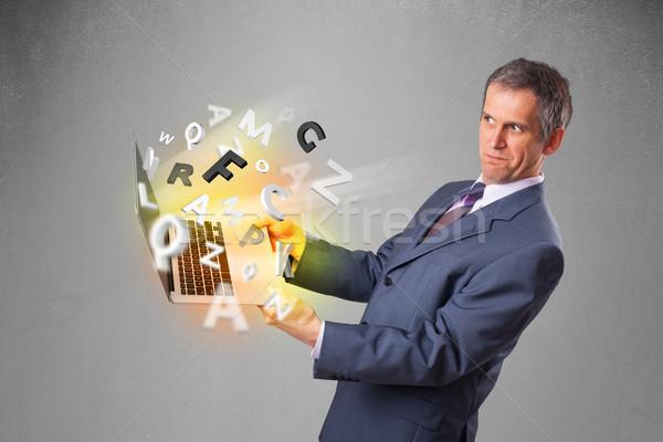 Középkorú üzletember tart laptop színes levelek Stock fotó © ra2studio