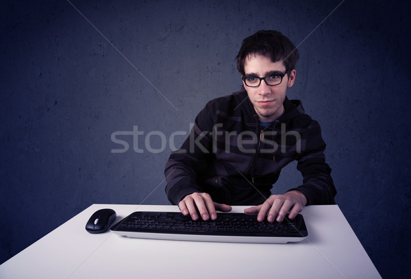 Hacker working with keyboard on blue background Stock photo © ra2studio
