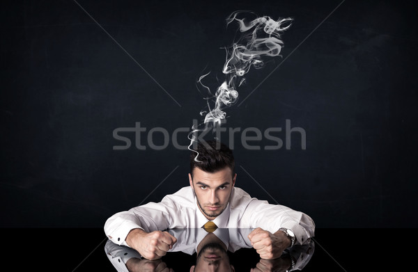 Depressed businessman with smoking head Stock photo © ra2studio