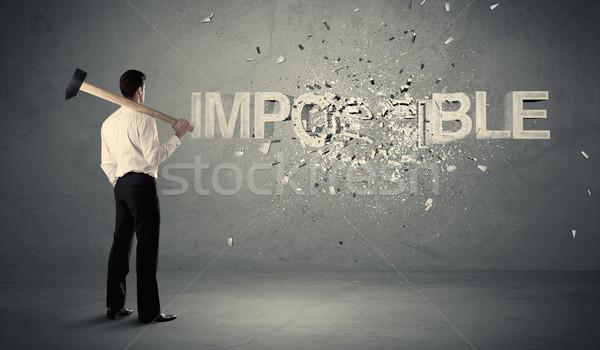 Uomo d'affari impossibile segno martello muro Foto d'archivio © ra2studio