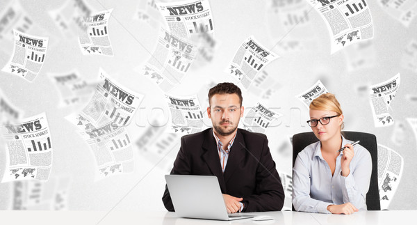Stock photo: Business man and woman at desk with stock market newspapers