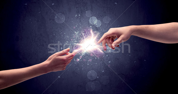 Hands reaching to light a spark Stock photo © ra2studio