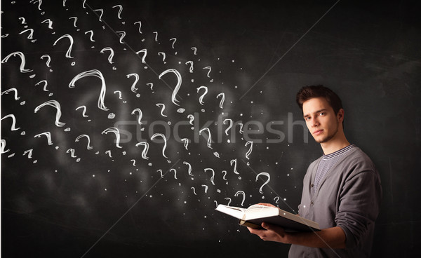 Young man reading a book with question marks coming out from it Stock photo © ra2studio