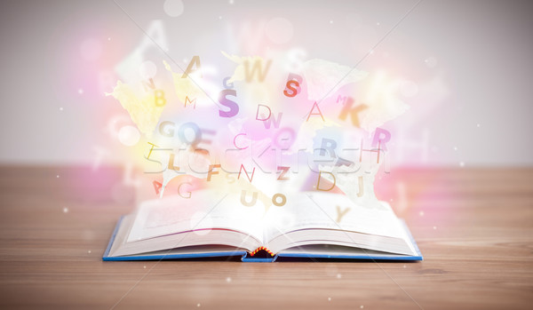 Open book with glowing letters on concrete background Stock photo © ra2studio
