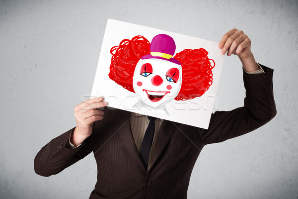 Businessman holding a cardboard with a clown on it in front of h Stock photo © ra2studio