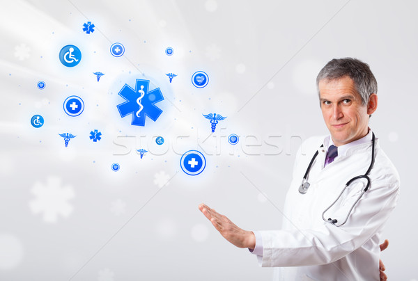 Doctor with blue medical icons Stock photo © ra2studio