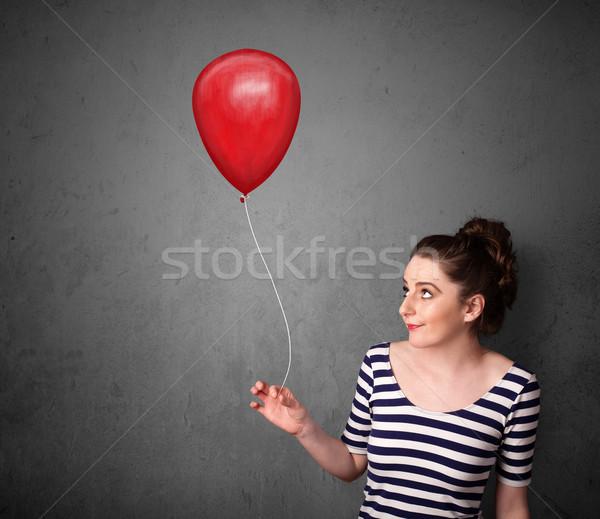 Woman holding a red balloon Stock photo © ra2studio