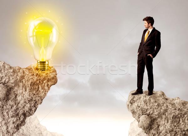 Businessman on rock mountain with idea bulb Stock photo © ra2studio