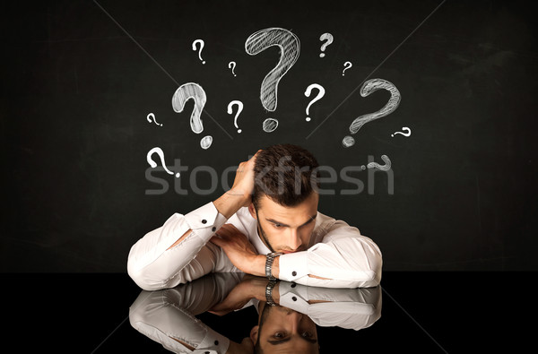 Sitting businessman under question marks Stock photo © ra2studio