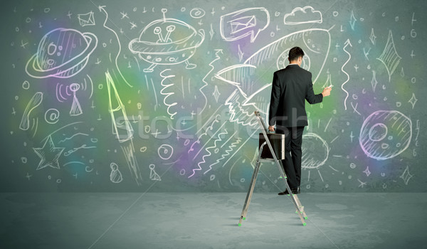 Stock photo: Young businessman drawing rocket