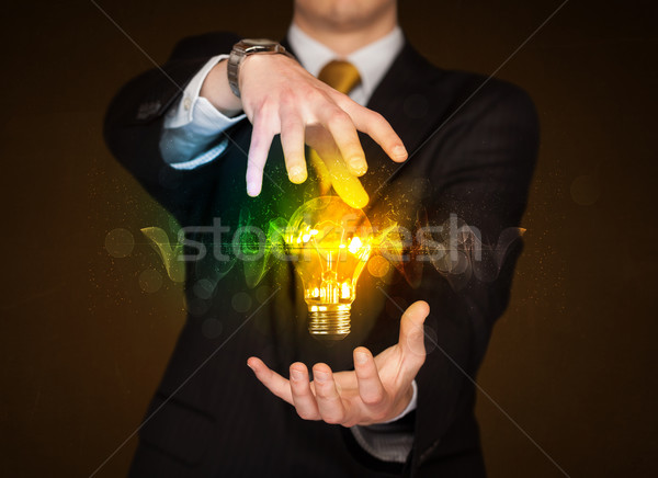 Businessman holding light bulb Stock photo © ra2studio