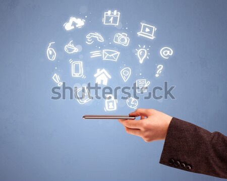 Hand holding tablet phone with drawn icons Stock photo © ra2studio