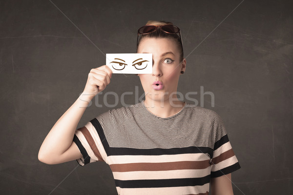 Young person holding paper with angry eye drawing  Stock photo © ra2studio