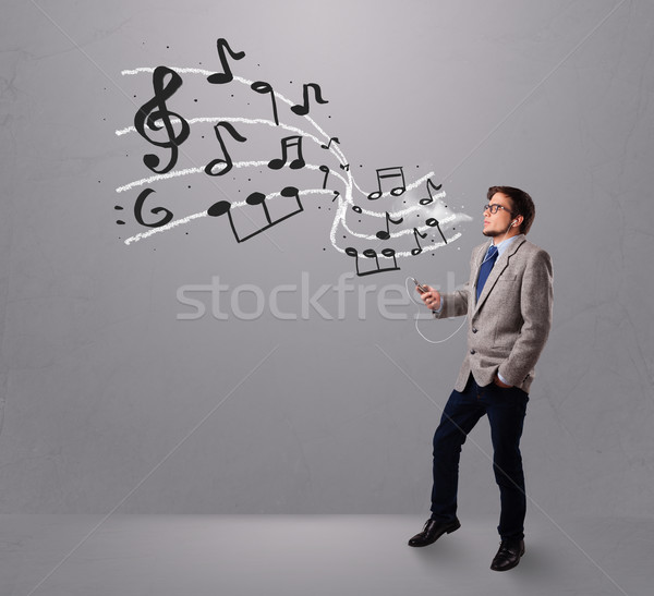 handsome boy singing and listening to music with musical notes  Stock photo © ra2studio